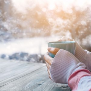 Side view of female hand holding hot cup of coffee in winter - Photo in vintage color image style.