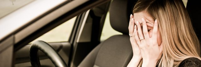 Young woman with hands on eyes sitting stressed in car.