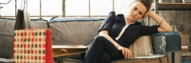 woman looking stressed after shopping sitting on sofa