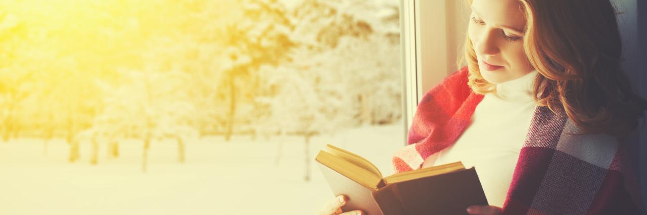 girl reading by window in winter