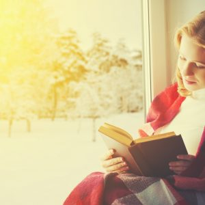 girl reading by window in winter