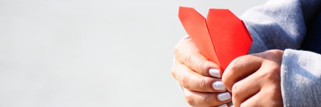 Hands Holding a Red Heart Shape Paper