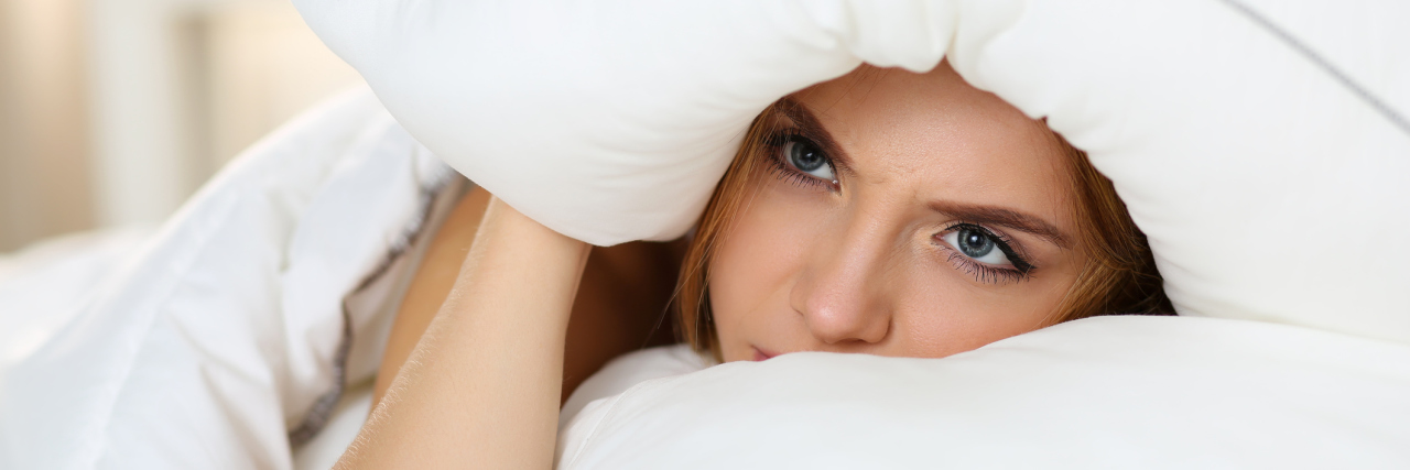 young woman lying in bed covering head with pillow