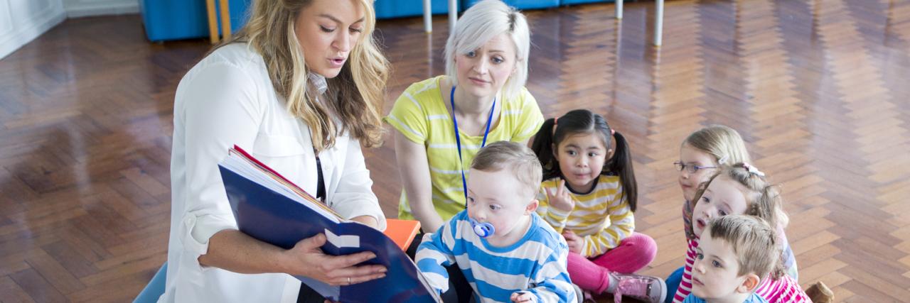 Children surrounding teacher reading a book.