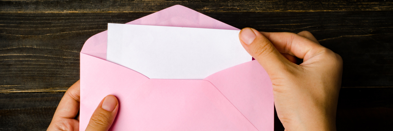 Pink envelope and blank white card are hold by hand