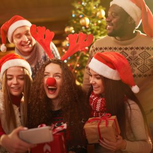 A group of friends taking a selfie in front of the Christmas tree, holding gifts and wearing antler headbands and Santa hats.