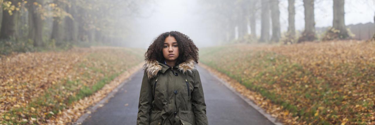 African-American girl walking alone in autumn.