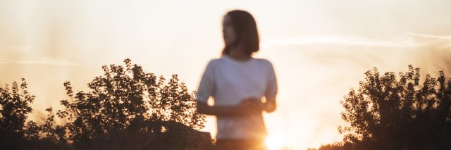 Young attractive brunette standing in the sunset summer field, contemplating. Photo with unusual focus