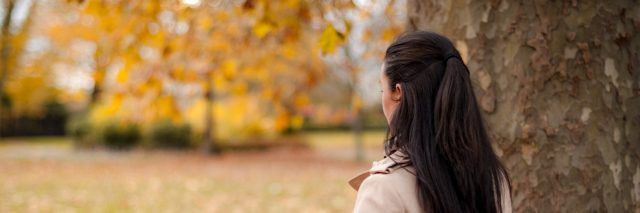 Woman standing next to tree in park during autumn