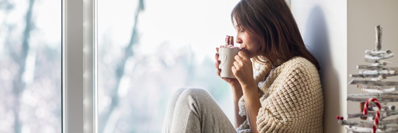 Young beautiful woman drinking hot coffee sitting on window sill