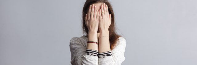 woman shame covering face with hands against plain background
