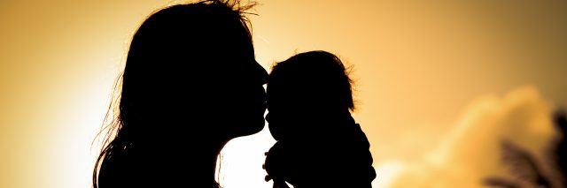 loving mother and kissing little baby play at sunset