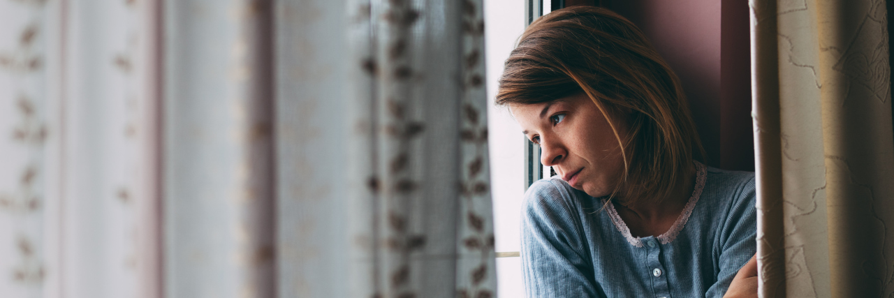 Young sad woman sitting on the window looking outside