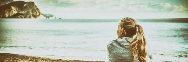 Woman sitting on beach hugging her knees and looking into the distance with hope.