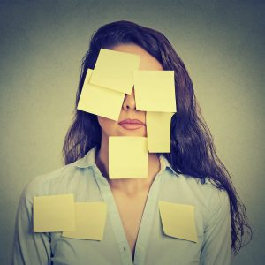 Woman who is covered by yellow post-it notes.
