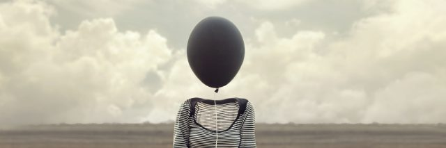 woman's head replaced by a black balloon