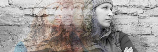 multiple exposures of young woman against brick wall with arms crossed