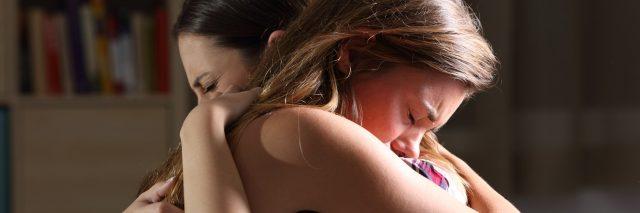 Two young women hugging.