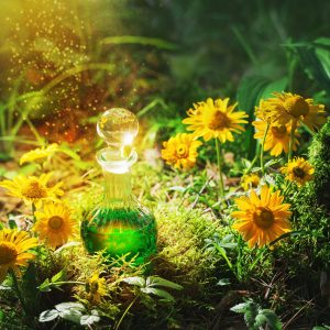 A bottle filled with green liquid, sitting in some grass, surrounded by yellow flowers with the sun shining down on it.