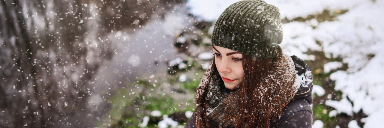 A downward image of a woman standing out in the snow, with a serious facial expression.