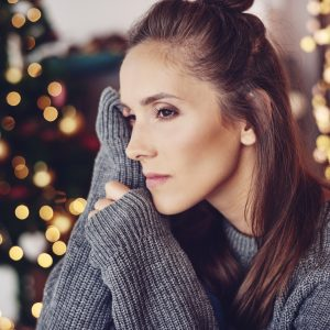 woman looking sad in front of a christmas tree