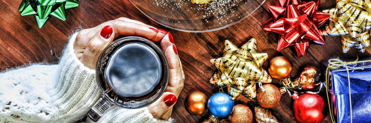 Woman holding a cup of tea, surrounded by holiday ornaments.