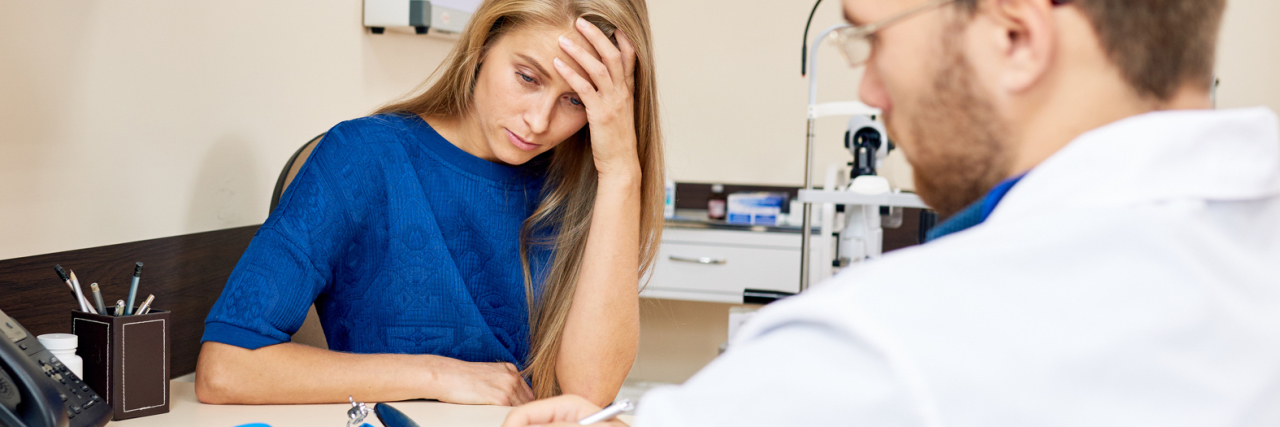 frustrated woman in doctor's office while doctor fills in form