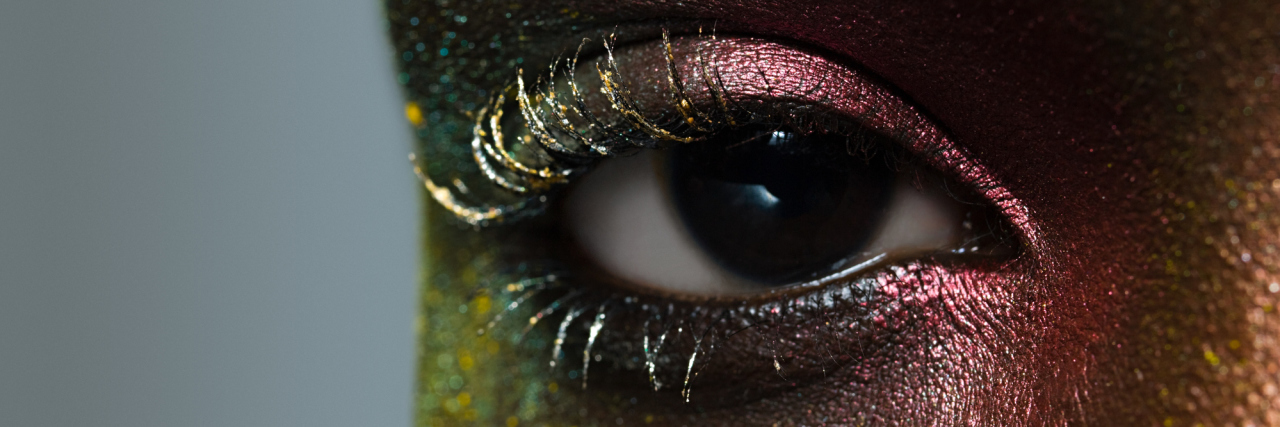 A close-up of an African American woman's eye, while she is wearing glitter makeup.
