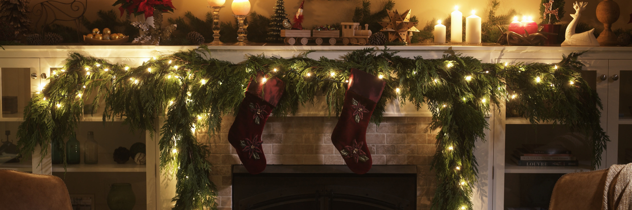 fireplace decorated with stockings and a wreath for christmas