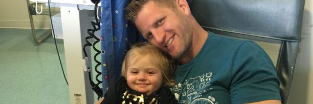 Father holding little girl at hospital