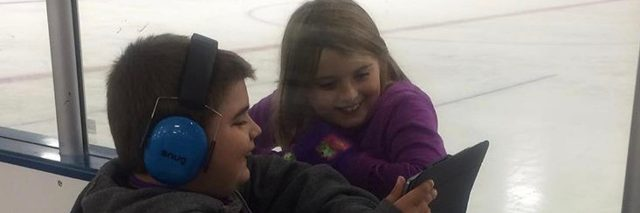 Boy wearing headphones showing a girl something on a tablet while at the skating rink.