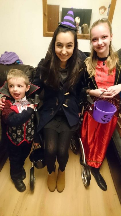 woman sitting on her rollator walker with her two younger siblings before going out trick or treating