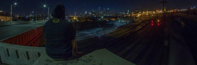 a man sits on a bridge overlooking a city