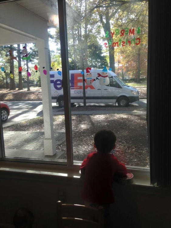 child looking out of a window at a Fedex truck