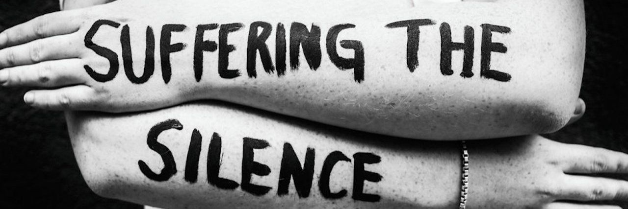 """suffering the silence"" painted on a woman's arms"