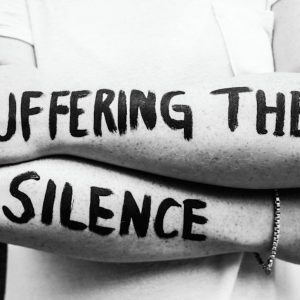 """""""suffering the silence"""" painted on a woman's arms"""