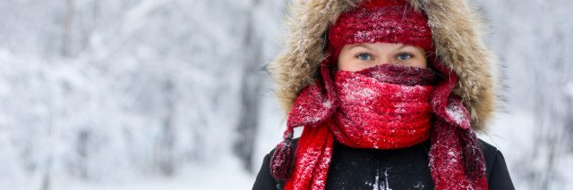 woman stands with scarf and hood over face during the winter