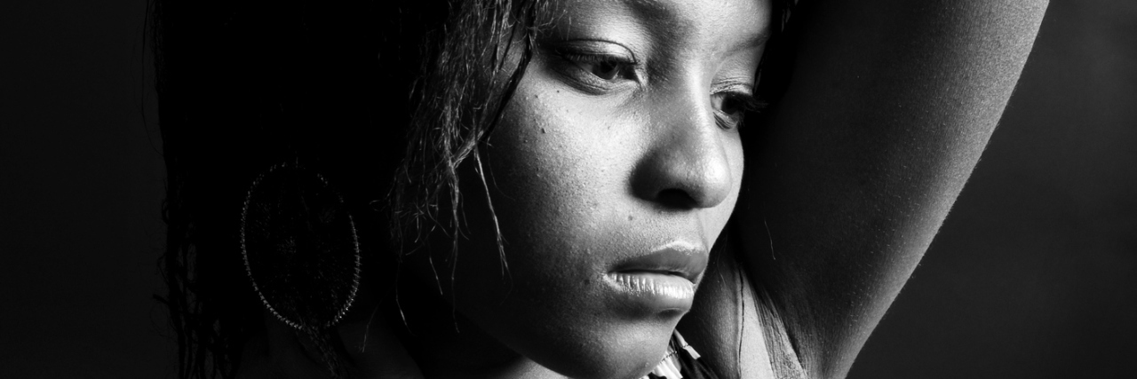 young woman in black and white looking upset against dark background