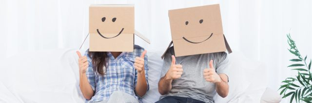 people sitting with boxes over their head and smiles drawn onto the boxes