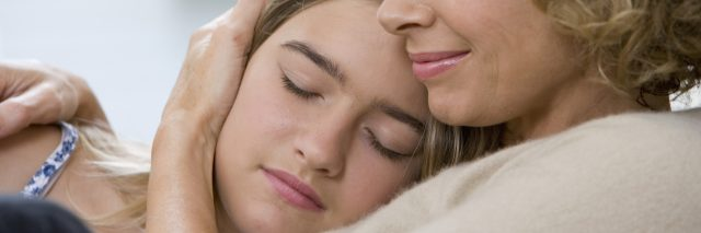 mother holding teenage daughter eyes closed close up
