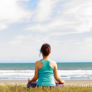 woman sitting alone on the beach looking at the ocean