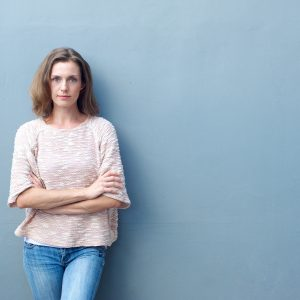 woman standing against a wall with her arms crossed