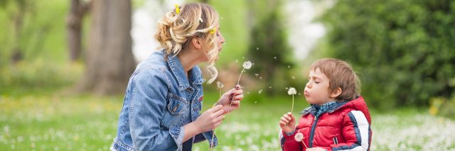 A mom and her young son blowing on dandelions in a park.