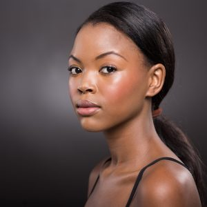 A beautiful African American looking at the camera with a serious expression.