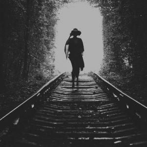 A silhouette of a woman in a dress and a hat walking on the rails in the natural tune