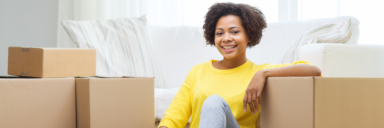 A young African American woman with boxes all around her in a home.