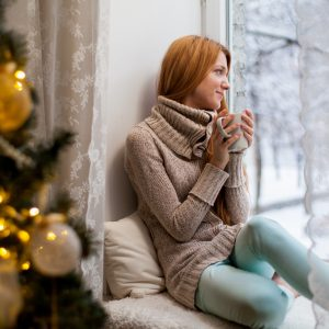woman sitting by a christmas tree looking out the window at snow