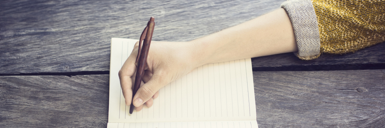 Girl with pen and blank diary on wooden table