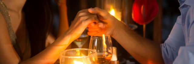 Romantic couple holding hands over candlelight during romantic dinner.