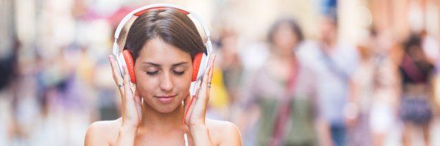 Woman wearing headphones walking down the street.